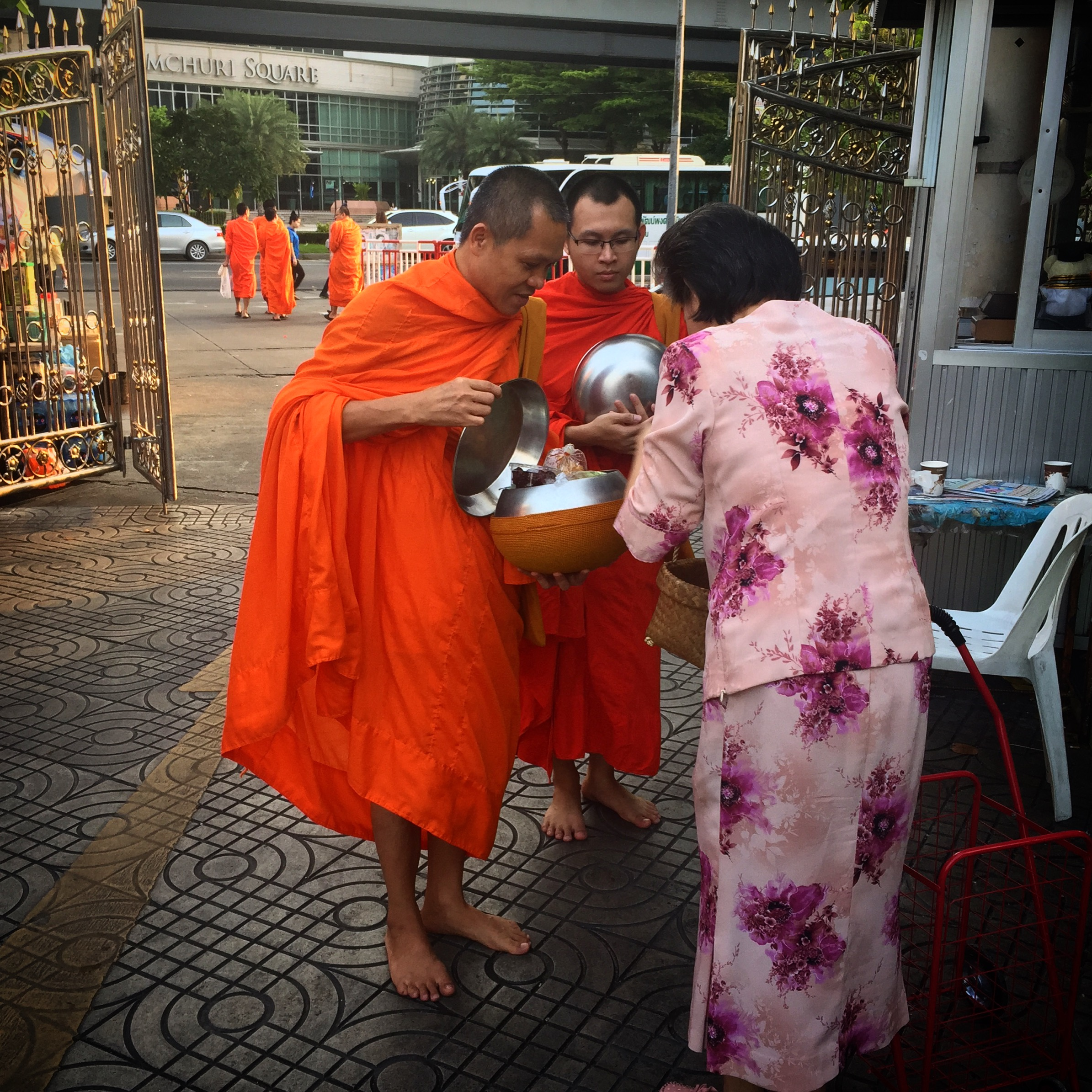 At dawn, bare footed monks leave the temple carrying their alms bowls